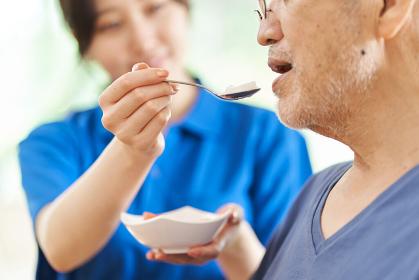 高齢者に食事の介助をする介護士