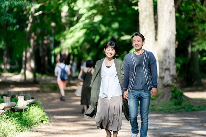 新緑の爽やかな小道を散歩するカップル(デート・夫婦)
