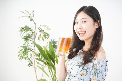 自宅でビールを飲む女性