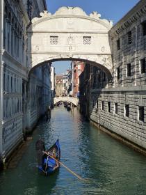 イタリア・ヴェネツィアにて細い運河と溜息の橋の下を通るゴンドラ