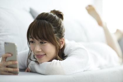 ソファでスマホを見る日本人女性