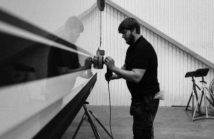 marine engineer polishing a boat in a marine warehouse