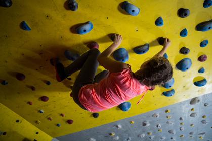 Teenage girl practicing rock climbing