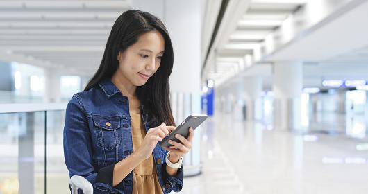 Woman using cellphone in Hong Kong airport