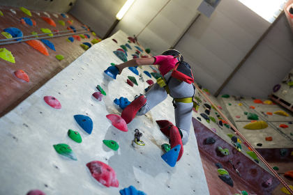 Teenage girl practicing rock climbing in fitness studio
