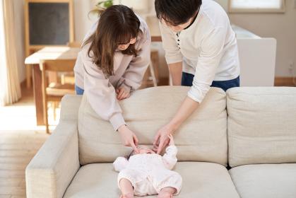 赤ちゃんのほっぺをつつくアジア人の夫婦