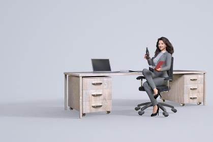木製の机にノートパソコンを置くパーマヘアのキャリアウーマンが椅子に座り瓶に入った炭酸飲料を片手に持つ