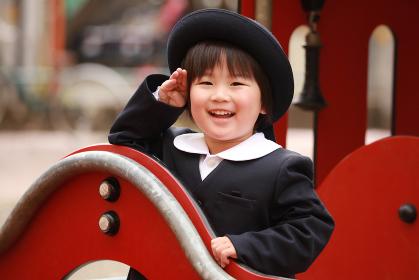 遊具に乗り敬礼する幼稚園児