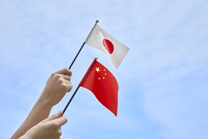 日本と中国の国旗を持つ手