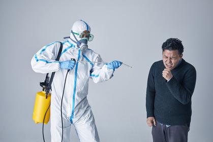 消毒をする防護服を着用した男性と日本人男性