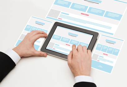 close up of hands with web design on tablet pc