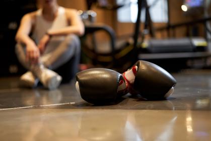 ボクシンググローブと、休憩するアジア人女性
