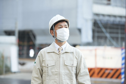 マスクをする作業着の日本人男性