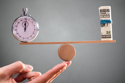 Hand With Balance Between Stopwatch And Rolled Up Banknotes
