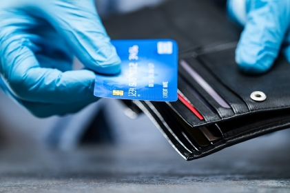 Consumer Holding Credit Card In Gloves