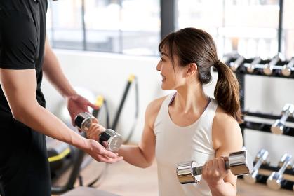 ダンベルトレーニングの指導を受けるアジア人女性
