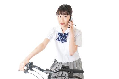 自転車でスマホを使う若い学生