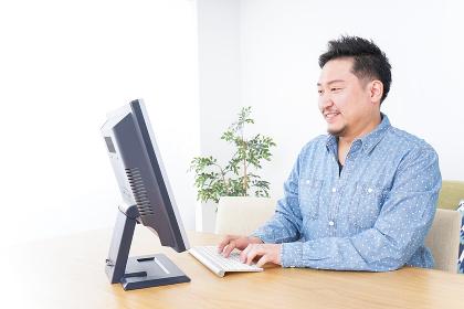 家でパソコンを使う男性