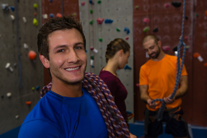 Portrait of man carrying climbing rope in gym