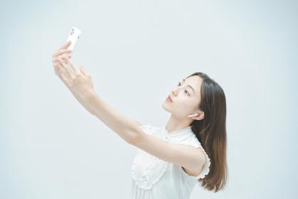 スマートフォンを持ちながら舞う若い女性