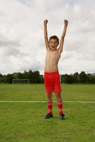 Young footballer with arms raised