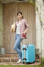 スーツケースを持ち旅行に出かける女性