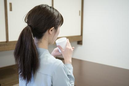 和室でくつろぐ若い女性の後ろ姿