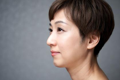 横を向いて微笑む中年の日本人女性