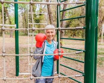 Happy Fit Senior Woman With Boxing Glove At Outdoor Gym