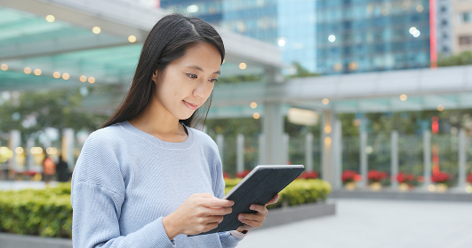 Asian woman working on tablet computer at outdoor