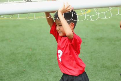 サッカーのゴールを運ぶ少年