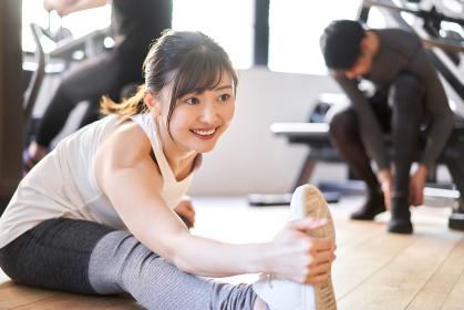 トレーニングジムでストレッチをするアジア人女性