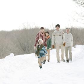 雪道を歩く3世代家族