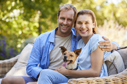 Happy young couple  sitting with their pet dog in the garden