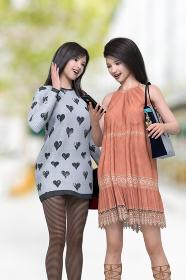 黒髪のロングヘアのワンピースを着た女の子2人が楽しそうにスマートフォンを見ながら会話している