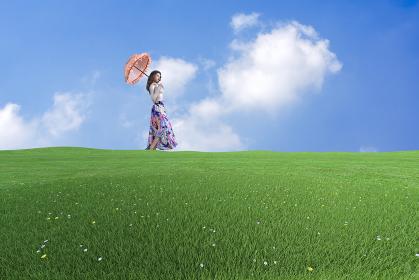 広い草原に1人佇む日傘をさしてカラフルなロングスカートを履いた女の子
