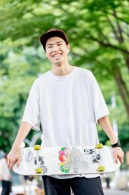 笑顔でスケートボードを手に持つ男性