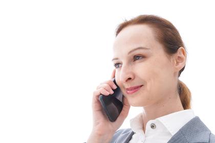 スマートフォンを使うスーツを着たビジネスウーマン