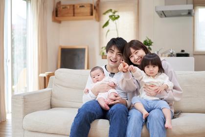 全員でテレビを見るアジア人ファミリー