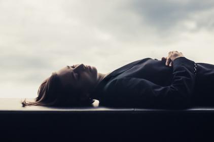 横たわる女性と夕方の空