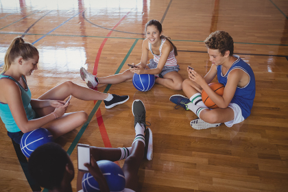 High school team using mobile phone while relaxing in the basketball court