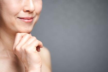 頬杖をついて微笑む中年の日本人女性