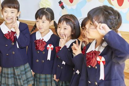 ピースサインをする笑顔の幼稚園児
