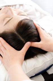 頭皮マッサージを受ける女性と施術者の手元