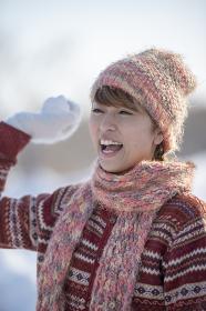 雪玉を持ち微笑む女性