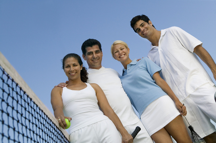 Four mixed doubles tennis players at net on tennis court portrait low angle view
