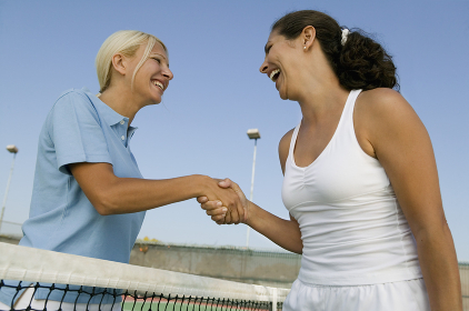 Two female Tennis Players shaking hand over tennis court net low angle view