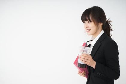 オフィスでアイスコーヒーを飲む若いビジネスウーマン