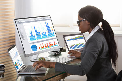 Businesswoman Looking At Graphs On Computer