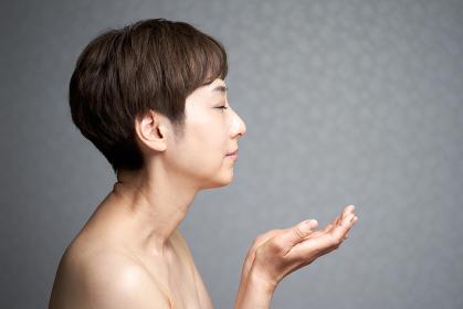 横顔で手を広げる中年の日本人女性